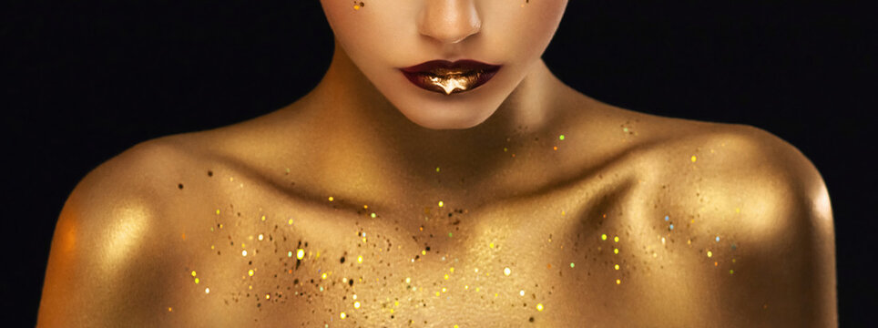 beauty fashion model girl's mouth close-up. Golden body skin. Glamour golden bright lipstick closeup. Liquid gold metal dripping from red lips. Beautiful artistic makeup shiny paint drop on woman face