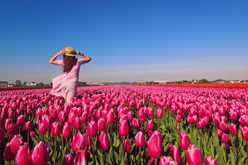 Woman tourist in pink dress and straw hat standing in tulip field