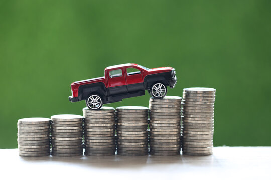 Miniature car model on growing stack of coins money on nature green background, Saving money for car, Finance and car loan, Investment and business concept