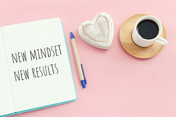 top view image of table with open notebook and the text new mindset new results. success and personal development concept