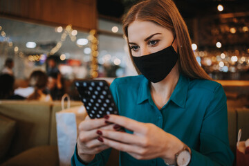 Beautiful young adult woman with protective face mask sitting in a nice restaurant and using her...
