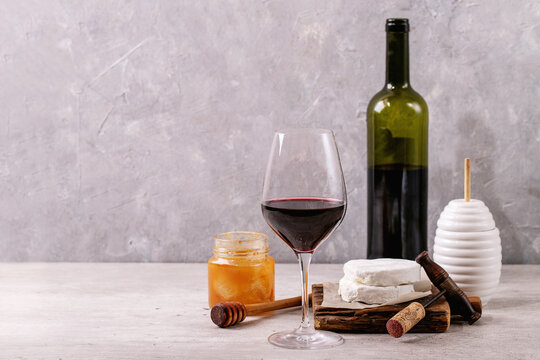 Goat cheese served with honey and bottle of red wine