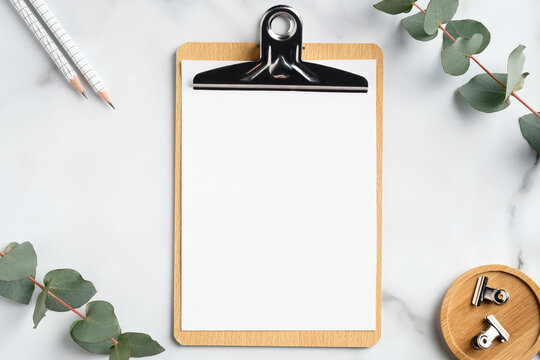 Mockup of wooden clipboard with blank paper on marble table with office supplies and eucalyptus branches. Top view with copy space, flat lay.