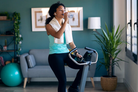 Sporty african young woman exercising on smart stationary bike while drinking water at home.