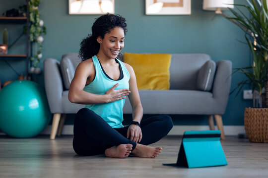 Afro sporty young woman doing hypopressive exercises following online gym classes via digital tablet on floor in her living room at home.