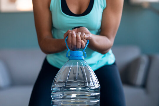 Afro beautiful gymnast woman doing exercices lifting eight liters water bottles in living room at home.