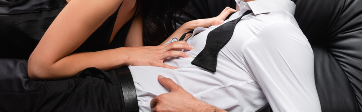 cropped view of passionate woman seducing man in untied tie, banner