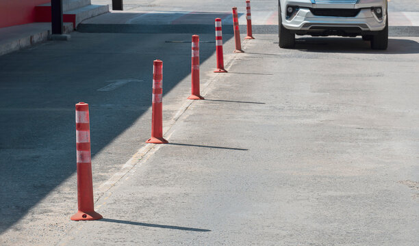 Row of orange plastic traffic poles with blurred motion front view of white car slow driving into outdoor parking lot area