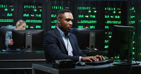 Smart African-American IT worker sitting in server room behind workplace working with database on computer. System software concept. - fototapety na wymiar