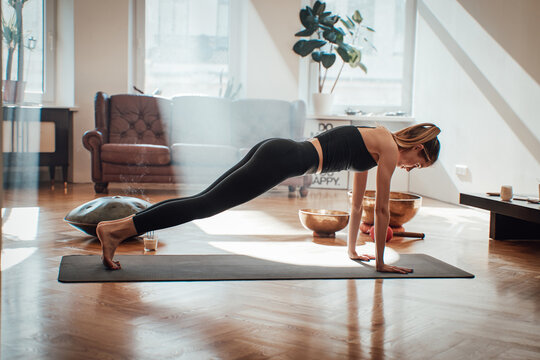 Relaxed and slim woman dressed in black sportswear works out doing yoga in pilates posture in shiny and warm living room in daytime.