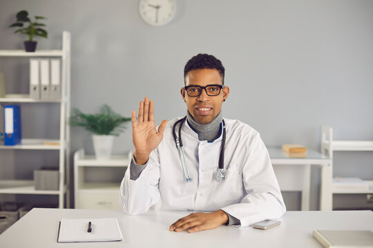 African-American online doctor in lab coat sitting at desk in his office and waving hand at camera, welcoming clients on medical video channel or saying hello or goodbye to patient during video call