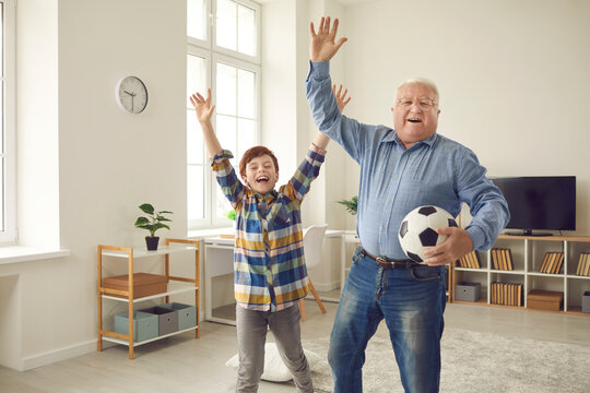 Excited grandfather and teen grandson enjoying free time, playing sports games together, having fun and celebrating victory of favorite soccer team. Happy childhood and active senior lifestyle concept