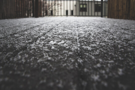 Winter nature background of fluffy white snow. Abstract contrast of fresh snow melting on wet wooden deck plank surface