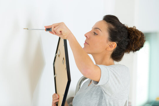 woman going to hang a frame