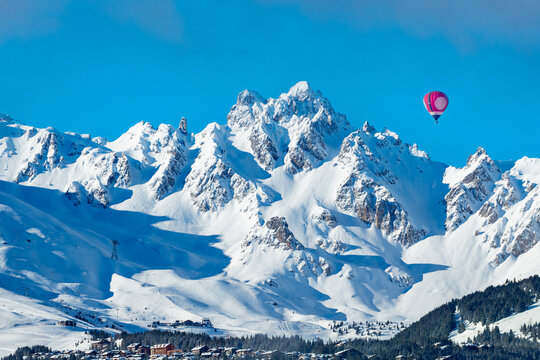 Vivid red colorful hot air balloon over Courchevel valley in French Alps