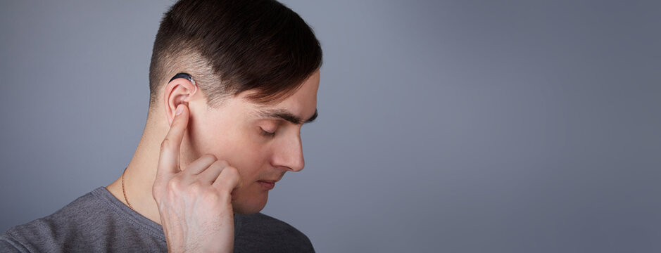 A young man is wearing a hearing aid. ENT equipment concept