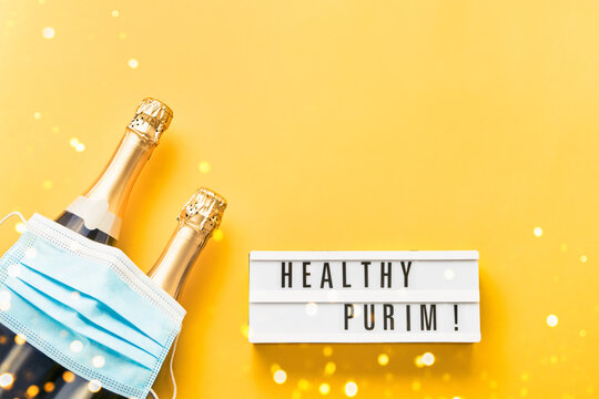 Healthy Purim written in lightbox, two champagne bottles, and medical mask on a yellow background.