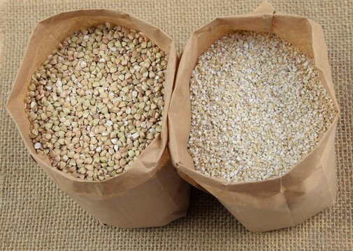 Buckhwheat unroasted and pearl barley, healthy groats in apper bags on jute fabric background