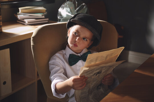 Cute little detective with newspaper in office