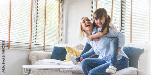 Happy Beautiful Mother carrying or piggyback her little daughter laughing playing and having fun together on sofa
