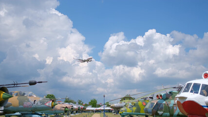 Passenger plane flying over the old planes open-air museum. Blue sky with clouds
