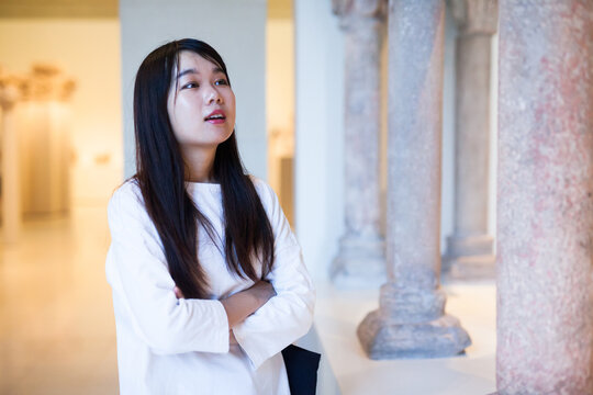 Young chinese woman visitor looking at exhibition in museum of ancient sculpture