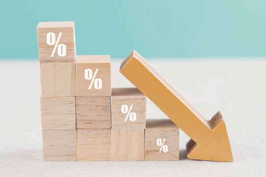 Wooden blocks with percentage sign and down arrow, financial recession crisis, interest rate decline, investment reduce, risk management concept