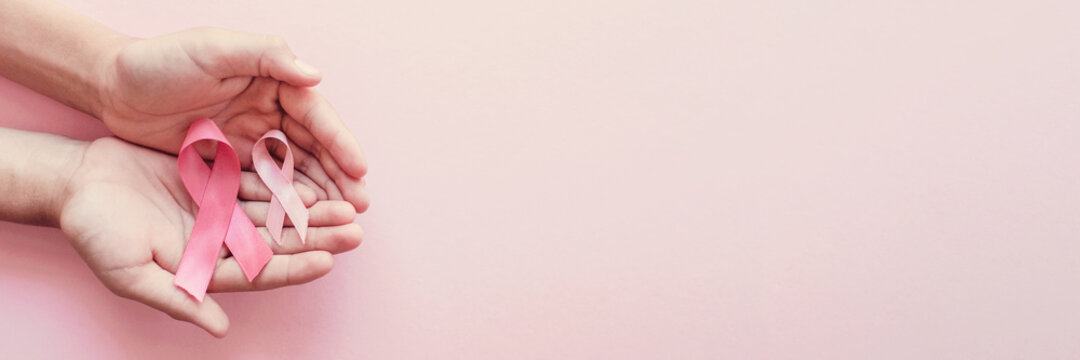 hands holding pink ribbons on pink background, Breast cancer awareness and October Pink , world cancer day