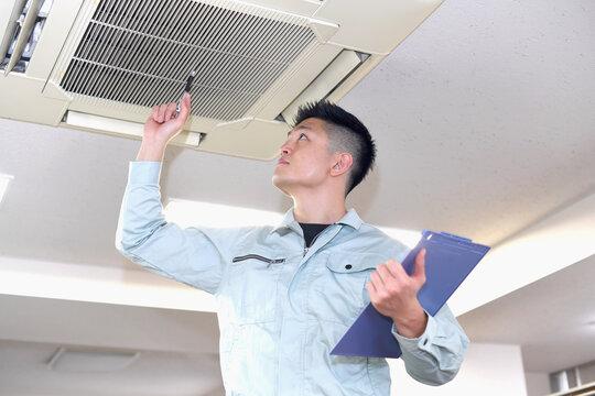 エアコンのメンテナンスをする作業服を着た男性