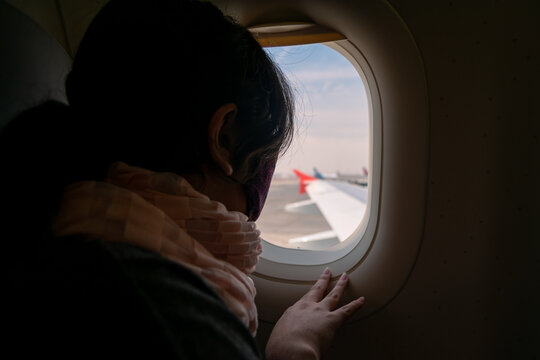 young woman with face mask looking out the window of an airplane