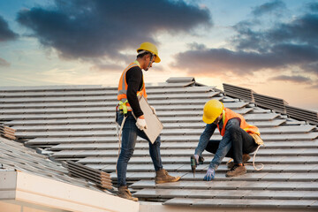 Obraz Asian engineer workers install new CPAC roof, roofing tools, electric drill, use on new roof with CPAC roof house construction idea. - fototapety do salonu