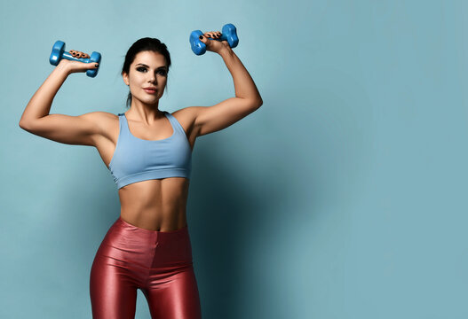 Fitness brunette woman in sportswear holds dumbbells in hands up showing her perfect muscles arms abs over light blue background with copy space. Perfect woman figure and healthy lifestyle concept
