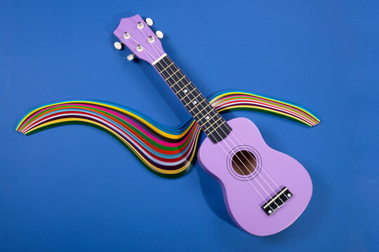 Four string ukulele guitar with a figure from colored paper