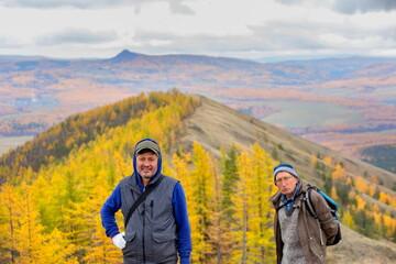 Fototapeta mature male tourists walk along the ridge of the big krak on an autumn day. obraz