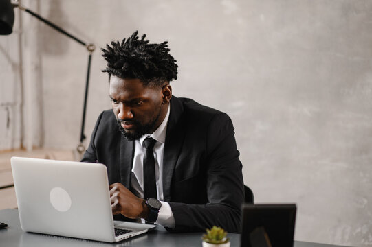 Handsome african american businessman in classic suit uses laptop and smiles while working in office