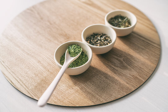 Green tea tasting, loose leaf dried leaves cups chinese teas rustic natural background. Spoon and teacups.