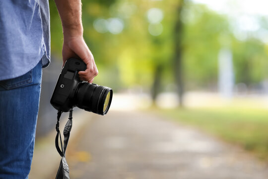 Photographer with professional camera in park, closeup