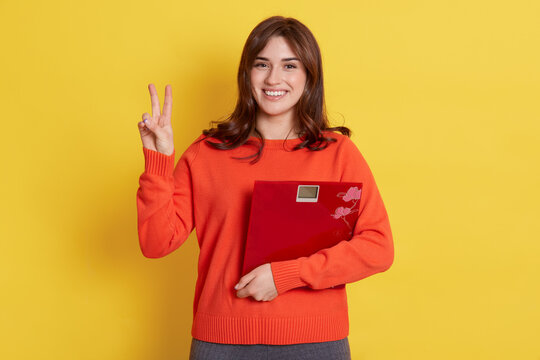 Attractive woman with scales in hands looks very happy, showing v sign, loosing weight, looks smiling directly at camera, wearing orange jumper, standing isolated over yellow background.