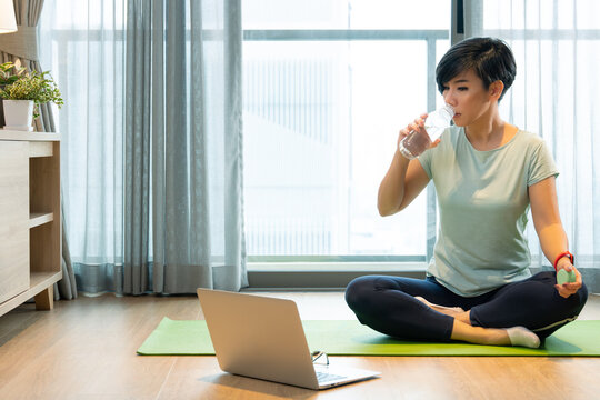 Home exercise during Covid 19 lock down. A healthy asian woman sit cross legs on a yoga mat, sip water from the bottle to keep her body stay hydrated. She watching online programs on laptop computer.