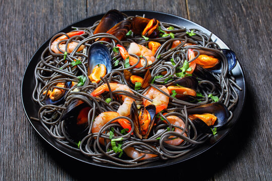 Squid ink pasta with mussels and shrimps, top view