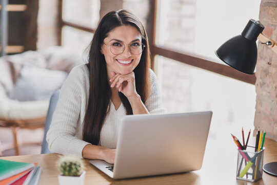Photo of successful lady sit table work netbook look camera arm chin wear specs white sweater in living room home indoors