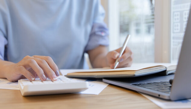 Head of accounting is recording the company's financial growth statistics using graphs as a reference for reviewing and analyzing the results, Taking notes and analyzing data graphs in office.