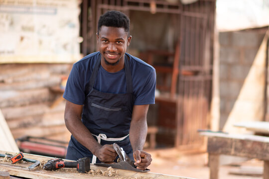 young african carpenter smiling while working