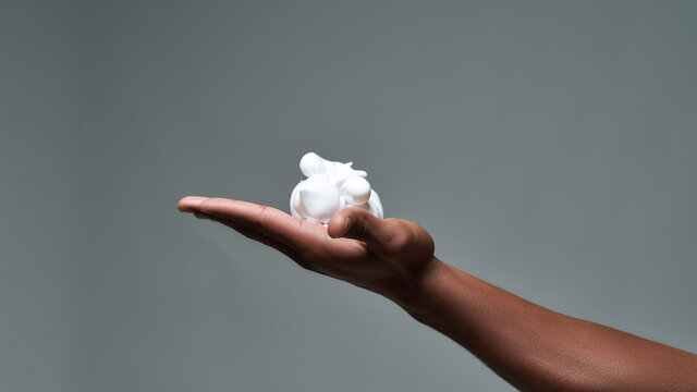Close up of hand of young african american man holding shaving foam, ready to shave isolated over gray background