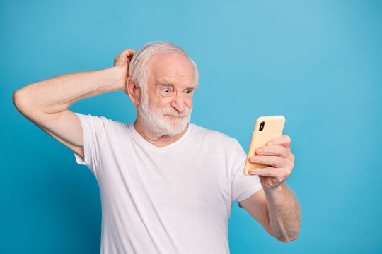 Portrait of unsatisfied person hand behind head staring phone grimace bad mood isolated on blue color background