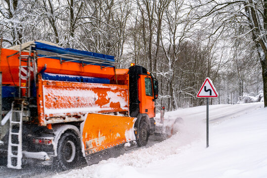 Snow ploughing truck cleans country road