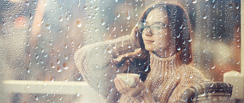 autumn coffee on a rainy day, girl behind a glass with a cup of hot coffee