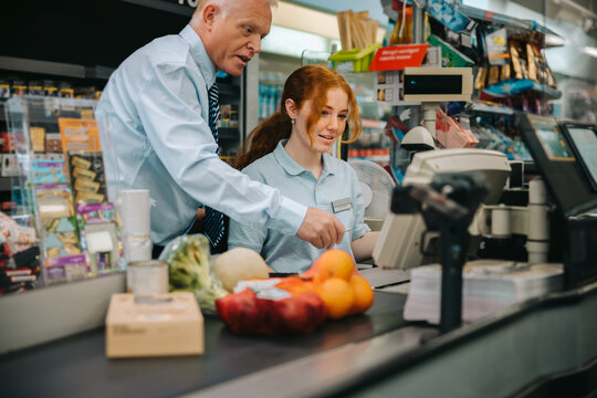 Manager teaching new employee at supermarket