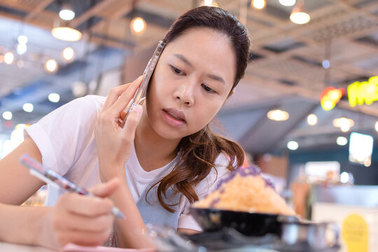 asian lady speaking on mobile phone in cafe