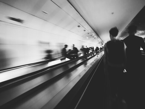 Long exposure of unrecognizable of commuters inside Parisian underground metro moving escalator walkway taking the fastest route to interchanges with other lines